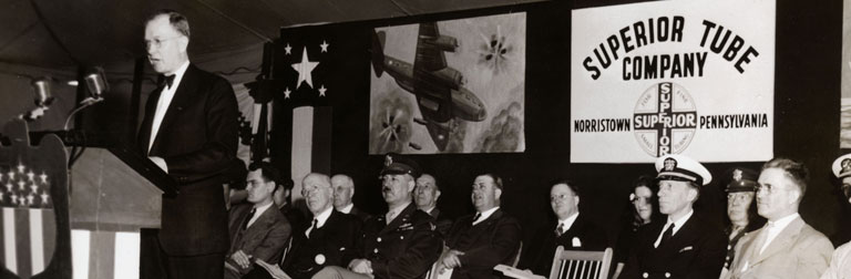 Navy-Army officers at an 'E' Award ceremony at Superior Tube. Speaking at the podium is Superior's General Manager S.L. Fabel
